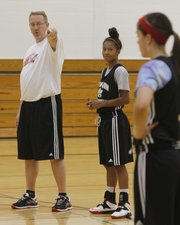 From left Lawrence High girls basketball coach Jeff Dickson instructs players Marissa Pope and Brook Sumonja during an LHS girls summer basketball camp, Thursday, June 5, 2014.