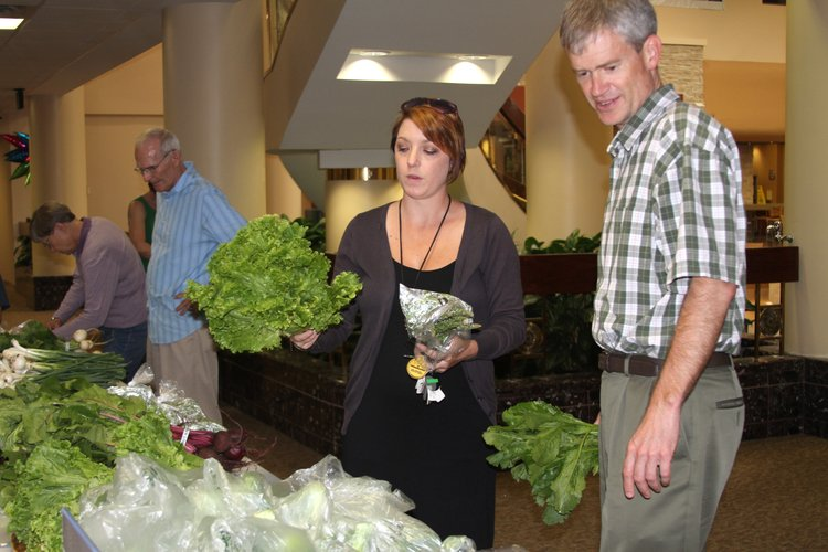 Aundrea Shafer, left, and Chris Tilden, both employees with the Lawrence-Douglas County Health Department, pick up fresh produce from a CSA program at Lawrence Memorial Hospital, which is across the street from the Health Department. The hospital and health department teamed up to offer a workplace CSA program to their employees.