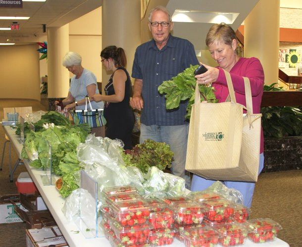 Paul Johnson, of East Stone House Creek Farm, visits with Lawrence Memorial Hospital employee LuAnn Baumchen as she picks up fresh produce as part of a CSA program.