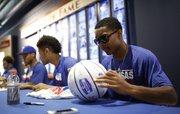 Kansas newcomer Devonté Graham and teammates sign items for basketball campers, Sunday, June 8, 2014, at Allen Fieldhouse.