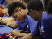 Kansas newcomer Kelly Oubre signs a jersey for a basketball camper along with the rest of the Jayhawks on Sunday, June 8, 2014, at Allen Fieldhouse.
