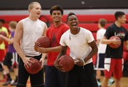 Lawrence High players Tae Shorter, front, Logan Shields and Price Morgan have a laugh after a missed dunk by a teammate as they get loose during warmups on Monday, June 9, 2014 at Lawrence High School.