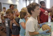 Mike Yoder/Journal-World Photo.Children react as they line up to hold a brain during an Exploratorium activity Monday at the Carnegie Building, 200 West 9th Street. The activity is one of a number of activities for kids 3 and up that is part of the Summer in the City reading program hosted by the Lawrence Public Library.