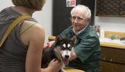 Veterinarian Herschel Lewis, 78, has been practicing in Lawrence the same way for decades: not taking appointments, no fancy equipment or technology. Here, he examines Kelly Farlow's dog, Skye, for a skin ailment at the clinic at 3101 W. Sixth St. on Friday.