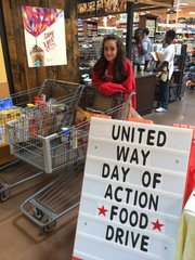 "Liberty Memorial Central Middle School eighth-grader Ana Hurt stands with two shopping carts filled with healthy food donations at Dillons, 1740 Massachusetts St., while participating in Douglas County United Way&squot;s ""Day of Action."""