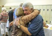 Longtime Lawrence Community Shelter director Loring Henderson, right, gets a big hug from Eileen Weiss, of Lawrence, during a retirement celebration honoring him at the Lawrence Community Shelter, 3655 E. 25th St. on Sunday afternoon.