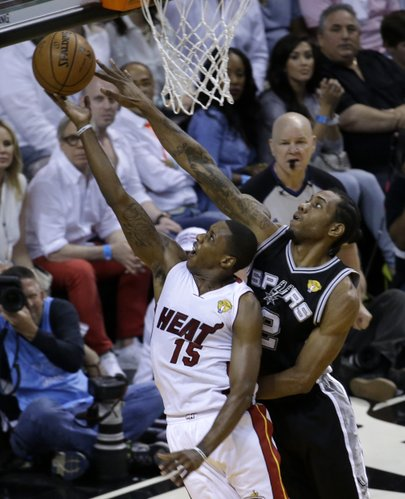 Miami Heat guard Mario Chalmers (15) goes to the basket as San Antonio Spurs forward Kawhi Leonard (2) defends in the first half in Game 4 of the NBA basketball finals, Thursday, June 12, 2014, in Miami. (AP Photo/Wilfredo Lee)