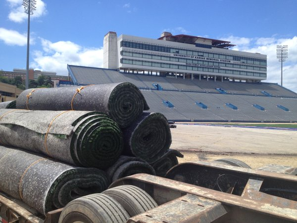 Rolls of new turf sit on a truck bed behind the south end zone at Memorial Stadium.