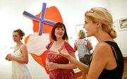"Paula Rose, center, co-curator of the ""YWAs: Young Woman Artists"" show at Wonder Fair, talks with Lawrence artist Kristin Morland during an artist&squot;s reception prior to the show&squot;s opening on Friday, June 27, 2014, at Wonder Fair, 803 1/2 Massachusetts St."