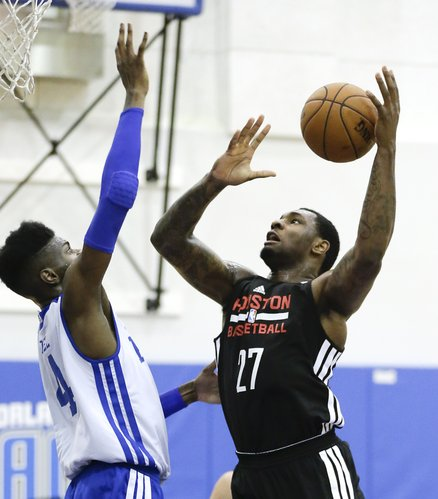 Houston Rockets' Tarik Black, right, tries to shoot over Philadelphia 76ers' Nerlens Noel in an NBA summer-league game, Tuesday, July 8, 2014, in Orlando, Florida.