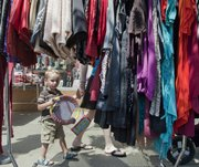 A young boy walks beneath a rack of women's clothes on Massachusetts Street during last year's Downtown Lawrence Sidewalk Sale. If you're going to this year's sale on July 17, make sure to have a game plan.