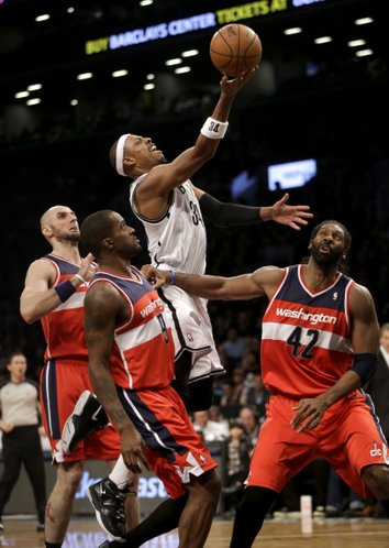 Brooklyn Nets' Paul Pierce, top, scores over Washington Wizards' Marcin Gortat, left, Nene Hilario, right, and Martell Webster during the second half of an NBA basketball game Wednesday, Dec. 18, 2013, in New York. Washington defeated Brooklyn 113-107. (AP Photo/Seth Wenig)