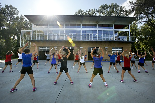 The Kansas University rowing team performs jumping jacks outside the boathouse on the Kansas River, Wednesday, Oct. 2, 2013.