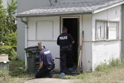 Mike Yoder/Journal-World Photo Lawrence police investigators dust for prints on a trash barrel in the backyard of a house in the 1100 block of New York Street during an investigation with the Kansas Bureau of Investigation officers Sunday morning, July 27, 2014.