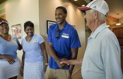 Miami Heat point guard and former Kansas University standout Mario Chalmers, center, greets former KU radio announcer Max Falkenstien during the Sixth Annual Mario V. Chalmers Foundation Golf Tournament & VIP Mixer at Alvamar Golf Club. At left are Mario's sister Roneka, and his mother Almarie.