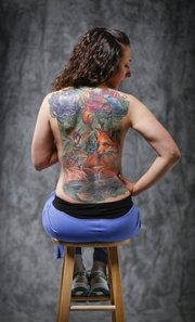 Katie Bledsoe's back features a natural scene to cover up three older tattoos that she no longer wanted. The full tattoo took 36 hours over several sessions to complete.