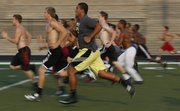 Lawrence High junior lineman Amani Bledsoe sprints the length of the football field with his teammates during morning workouts on Thursday, July 31, 2014.