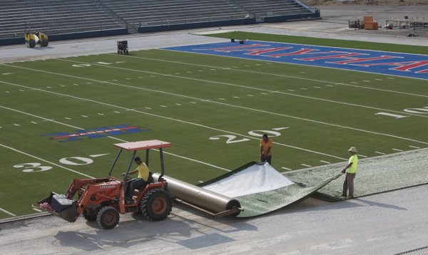 Workers roll out turf in areas previously covered by running track, Thursday, July 31, 2014, at Memorial Stadium. Installation of the turf — one of the final steps in a six-week stadium upgrade — began early Thursday and is expected to be finalized over the weekend.