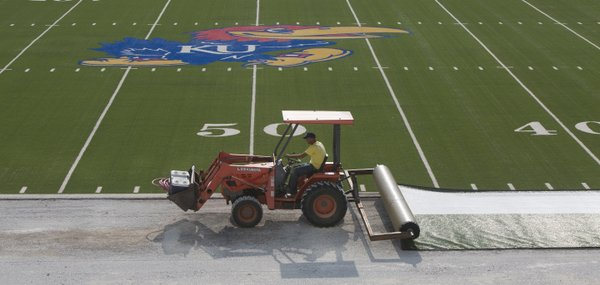 Jim Kaltmayer rolls out turf in an area previously covered by running track, Thursday, July 31, 2014, at Memorial Stadium. Installation of the turf — one of the final steps in a six-week stadium upgrade — began early Thursday and is expected to be finalized over the weekend.