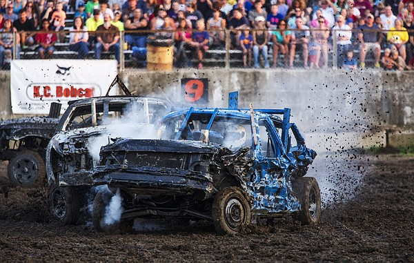 Smoke pours from under the hood and mud flies from the back tires of Jimmy Thompson's 1991 Crown Victoria as he swaps metal with Clint Doherty during the full-size class round of the demolition derby at the 2014 Douglas County Fair.