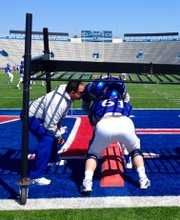 Kansas University offensive coordinator and offensive-line coach John Reagan gets down to pad level with a couple of KU lineman during a spring practice in March at Memorial Stadium.