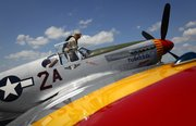 "Lawrence native and volunteer air show pilot Bill Shepard sits back into the cockpit of a P-51 C Mustang plane called ""Tuskegee Airmen"" in front of his assistant, Marvona Welsh, while preparing to take off from Lawrence Municipal Airport on Monday, August 11, 2014. The restored 1940s plane is named in honor of the Tuskegee Airmen, the famous all-black group of pilots who flew similar airplanes in World War II."