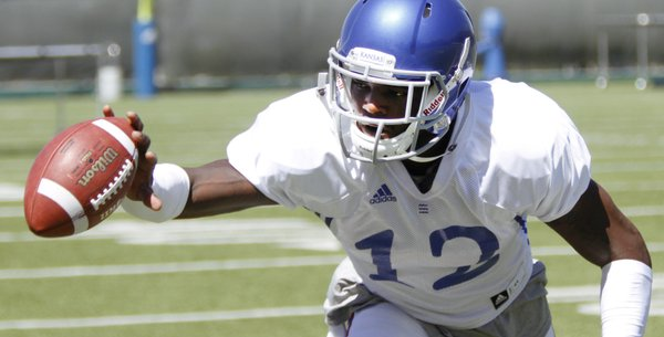 KU defensive back Dexter McDonald (12) knocks down a pass during team drills Tuesday, August 12.