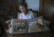 Margaret Shirk, shown at age 97 in rural Lawrence, displays an album of Jayhawk memorabilia. She said she hadn't missed a KU men's home basketball game since 1940 —unless the game coincided with an election, in which case she was working at the polls.