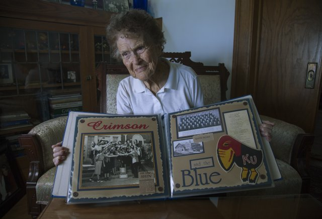 Margaret Shirk, shown at age 97 in rural Lawrence, displays an album of Jayhawk memorabilia. She said she hadn't missed a KU men's home basketball game since 1940 — unless the game coincided with an election, in which case she was working at the polls.