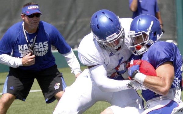 Kansas University linebacker Kyron Watson, (6) center, tackles running back  Brandon Bourbon (25) during a team practice Thursday, August 14, 2014. Linebacker coach Clint Bowen is at left.