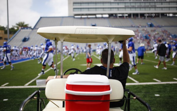 Kansas head coach Charlies Weis watches warmups from a golf cart during Fan Appreciation Day, Saturday, Aug. 16, 2014 at Memorial Stadium.