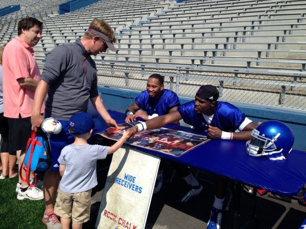 KU receivers Nick Harwell (left) and Justin McCay meet a young fan in the autograph line after the practice.