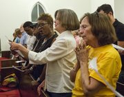 Barbara Johnston, right, of Baldwin, claps her hands together while Susie Brooks, center, and Delores Lang-Patton, both of Lawrence, share a song sheet as the women join in song during vigil for Michael Brown and other victims of racial violence Thursday evening at St. Luke AME Church, 900 New York.