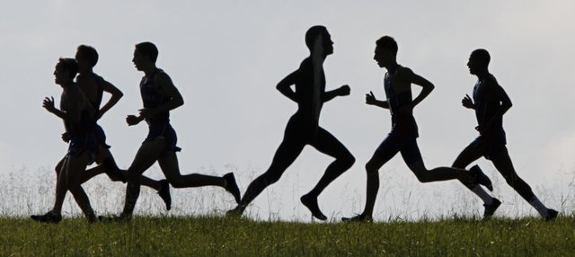 Runners participating in the Bob Timmons Dual Classic cross country meet run along the Jim Ryun skyline and past the metal silhouetted image of former KU runner John Lawson, Saturday, Aug. 30, 2014, at Rim Rock Farm.