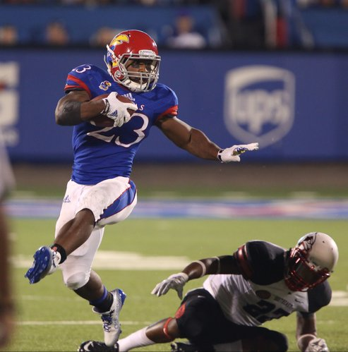 Kansas running back De'Andre Mann tries to stiff arm Southeast Missouri State safety Ron Davis during the fourth quarter on Saturday, Sept. 6, 2014 at Memorial Stadium. At right is Redhawks linebacker Wisler Ymonice.