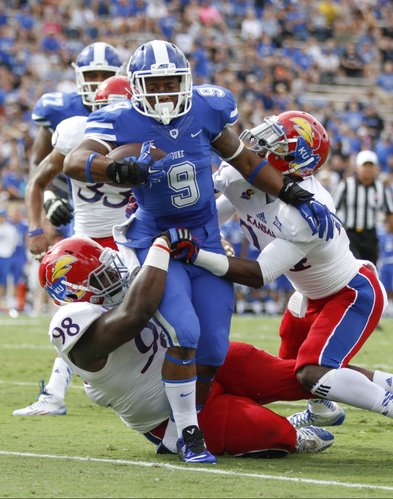 Duke running back Josh Snead breaks through Kansas defenders Keon Stowers, left, and JaCorey Shepherd during the first quarter on Saturday, Sept. 13, 2013 at Wallace Wade Stadium in Durham, North Carolina.