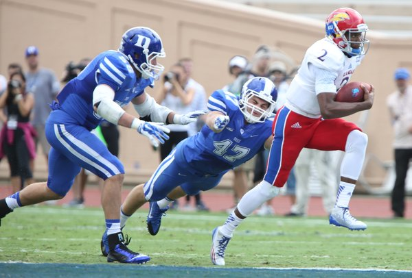 Kansas quarterback Montell Cozart is tailed by Duke defenders Kyler Brown (56) and David Helton (47) during the first quarter on Saturday, Sept. 13, 2013 at Wallace Wade Stadium in Durham, North Carolina.