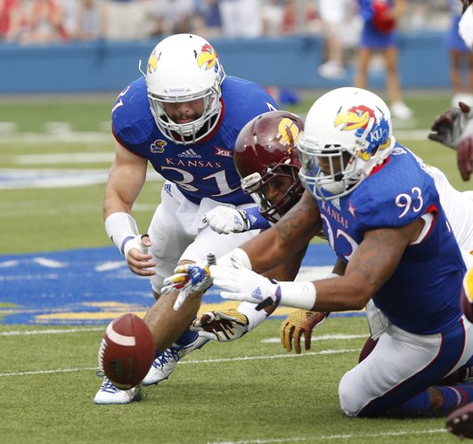 From left, KU Senior Ben Heeney (31) and junior Ben Goodman (93) go after a fumble against Central Michigan's Anthony Garland (44) on Saturday, September 20, 2014 at Memorial Stadium.