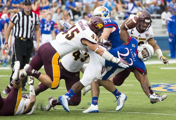 Kansas junior running back De'Andre Mann (23) fights for extra yardage against the Central Michigan defense during their game on Saturday afternoon at Memorial Stadium.