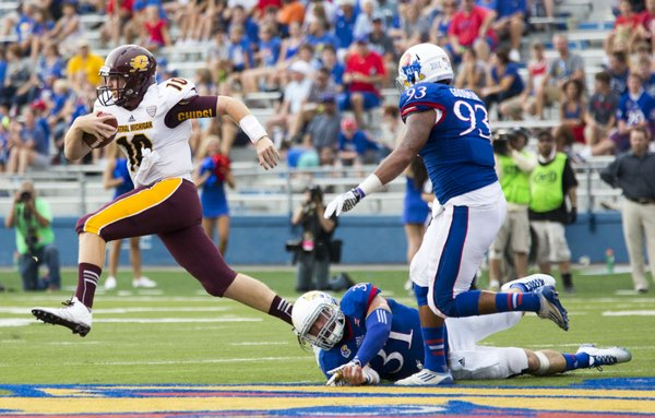 Central Michigan quarterback Cooper Rush (10) escapes from Kansas' Ben Heeney (31) and Ben Goodman (93), scrambling for a first down during their game on Saturday afternoon at Memorial Stadium.