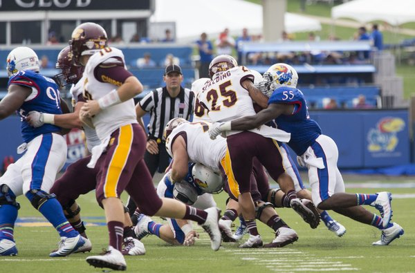 Kansas senior Michael Reynolds (55) pulls down Central Michigan running back Devon Spalding (25) for a loss during their game on Saturday afternoon at Memorial Stadium.