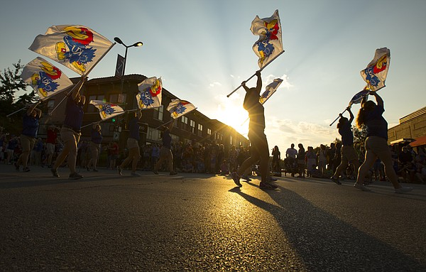 Flag twirlers lead the Kansas University marching band during the 2014 Kansas University Homecoming Parade, Friday, Sept. 26  2014 in downtown Lawrence.