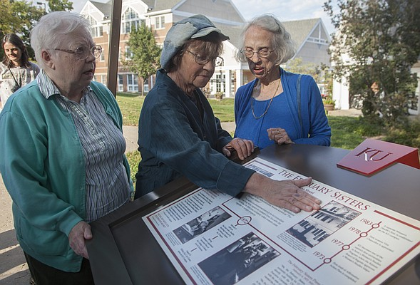 C.J. Brune, center, touches a historical marker that was unveiled Tuesday, Sept. 30, 2014, by Kansas University and KU Endowment honoring the women known as the February Sisters, who occupied the former East Asian Studies Building on Feb. 4, 1972, to demand equal rights, safety and justice for women at KU. From left are Marilyn Stokstad, KU distinguished professor emerita of art history, Brune, who was one of the February Sisters who occupied the building and Elizabeth Schultz, professor emerita of English at KU, who helped deliver food to the occupiers and helped commission the marker. The marker is north of 1346 Louisiana St. near the former East Asian Studies building.