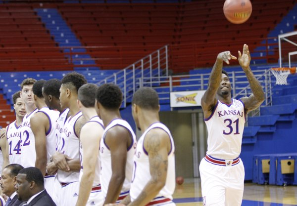 Junior forward Jamari Traylor attempts a long 3-point basket before a team photograph during the 2014 KU men's basketball team media day, Oct. 2, 2014.