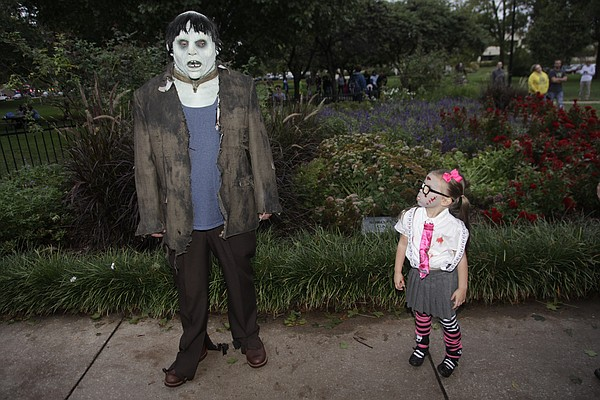Maisy Mack, 4, Eudora, right, checks out a nearby zombie during the 8th annual Lawrence Zombie Walk Oct. 2, 2014.