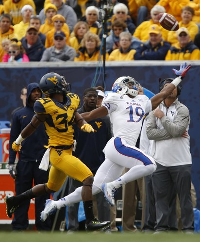 A deep pass to Kansas receiver Justin McCay goes long as he is trailed by West Virginia cornerback Ishmael Banks during the first quarter on Saturday, Oct. 4, 2014 at Milan Puskar Stadium in Morgantown, West Virginia.
