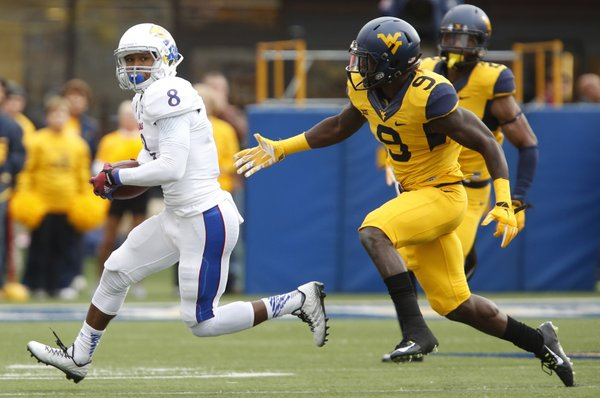 Kansas receiver Nick Harwell looks to escape West Virginia safety KJ Dillon during the first quarter on Saturday, Oct. 4, 2014 at Milan Puskar Stadium in Morgantown, West Virginia.