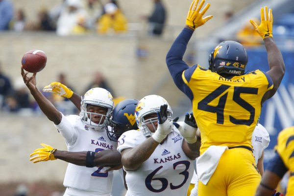 Kansas quarterback Montell Cozart takes a helmet-to-helmet hit from West Virginia safety Karl Joseph while releasing a pass during the second quarter on Saturday, Oct. 4, 2014 at Milan Puskar Stadium in Morgantown, West Virginia. Also pictured are KU offensive lineman Ngalu Fusimalohi and WVU defensive lineman Eric Kinsey.