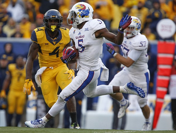 Kansas safety Isaiah Johnson makes a cut while returning an interception against West Virginia during the third quarter on Saturday, Oct. 4, 2014 at Milan Puskar Stadium in Morgantown, West Virginia.