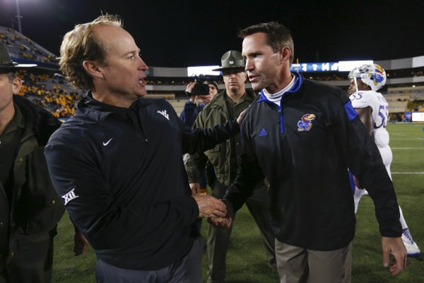West Virginia head coach Dana Holgorsen and Kansas interim head coach Clint Bowen meet at midfield to shake hands following the Jayhawks' 33-14 loss to the Mountaineers on Saturday, Oct. 4, 2014 at Milan Puskar Stadium in Morgantown, West Virginia.